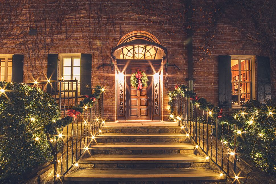 The entrance to Misselwood House at night decorated for the holidays with lights and greenery