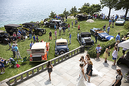 Concours event guests on back porch and vintage cars on the Misselwood back lawn