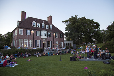 People sitting on Misselwood back lawn listening to live music with Misselwood House in the background
