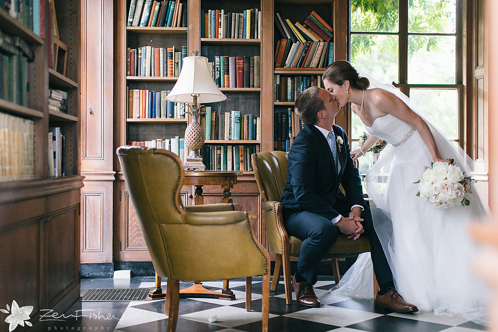 Bride and groom kissing in Misselwood House library